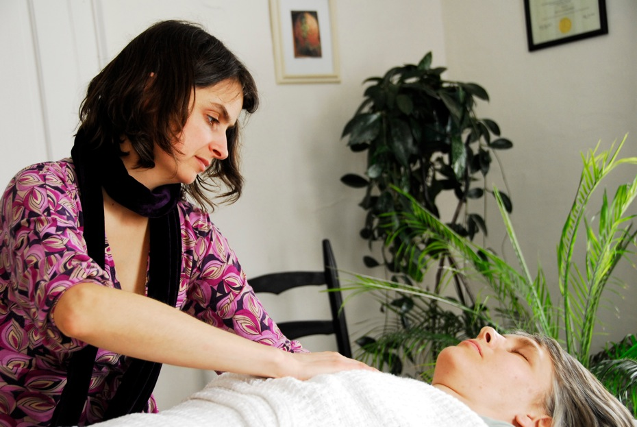 Woman with hands over heart on client who is very relaxed under a blanket on the healing table with plants in the background