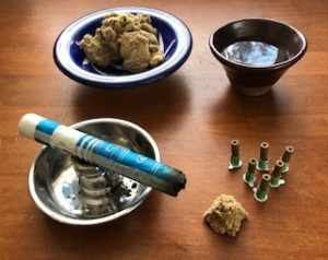 Moxa Pole on silver colored holder, loose moxa in blue and white dish, cup of water, stick on moxa and moxa cone on wooden table