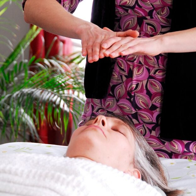 Hands held over relaxed client at the close of an energy healing session